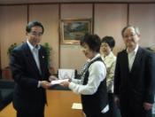 集まった募金を福井市長に渡している様子